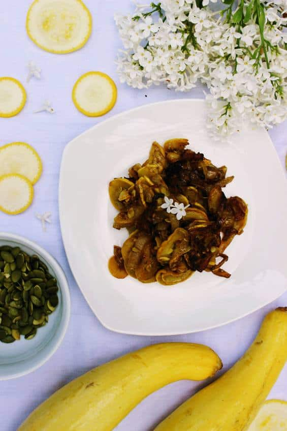Overhead shot of keto yellow squash and onions on white plate with white tablecloth with 2 whole yellow squash nearby and slices of yellow squash and white lilacs decorating the table