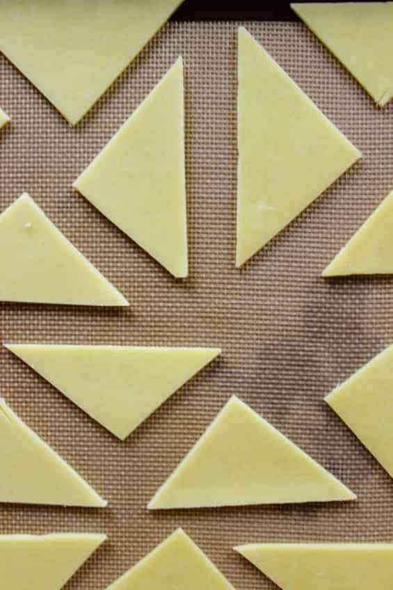 Overhead shot of uncooked cheese slices on baking sheet prior to baking for cheese chips