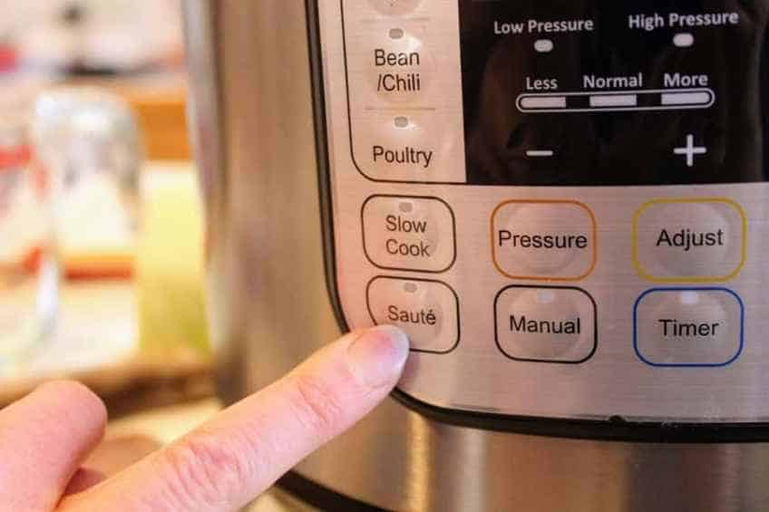 Finger pointing at saute setting on instant pot for corned beef and cabbage soup low carb recipe