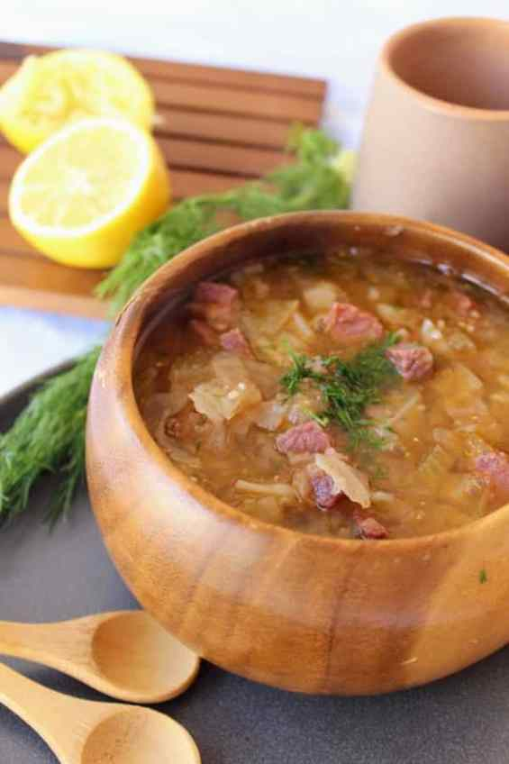 Corned Beef and Cabbage Soup in a wooden monkey pod bowl with fennel fronds sprinkled on top and lemon halves in the background