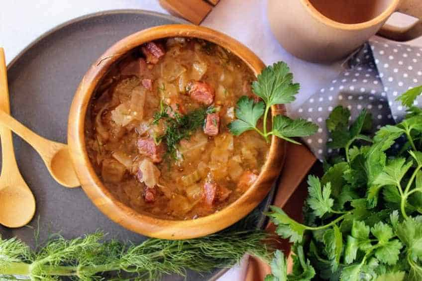 Overhead shot of stylized bowl of corned beef and cabbage soup on a slate gray plate with wooden spoons, gray and white polka-dotted napkin, and a bunch of parsley to the side for corned beef and cabbage soup low carb recipe
