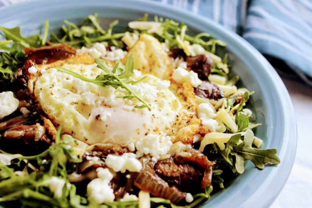 Keto arugula egg breakfast bowl with caramelized onions and mushrooms topped with crumbled goat cheese and Gouda